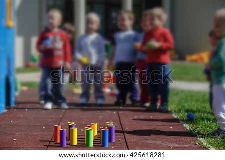 Children playing with homemade, do-it-yourself educational toys, tube bowling. Learning through experience concept, gross and fine motor skills, educational approach concept. - stock photo