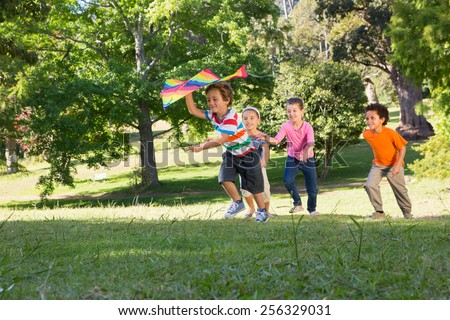 Children playing with kite in park on a sunny day - stock photo