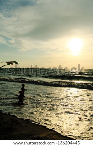 Children playing with kite on the sea