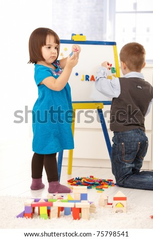 Children playing with magnetic drawing board and alphabet.? - stock photo