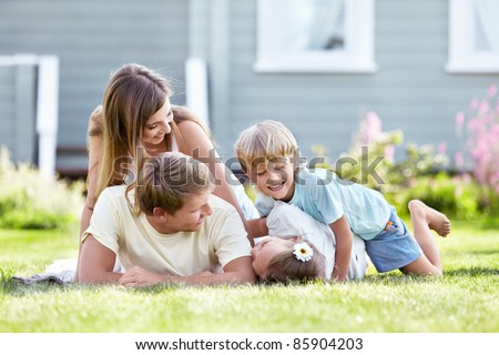 Children playing with parents in the garden - stock photo