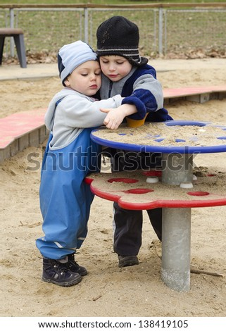 Children playing with sand in a playground on a cold day. - stock photo