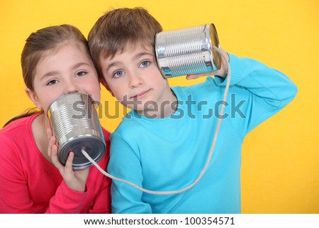 Children playing with tin cans - stock photo