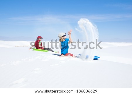 Children playing with white sand, throw it in the air.  White Sands, New Mexico, USA - stock photo