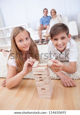 Children Playing With Wooden Blocks And Parents Behind Them At Home