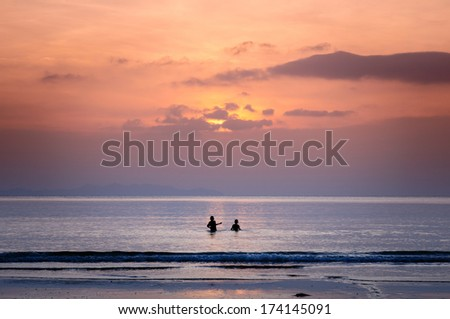children plays at the beach during sunset