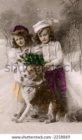 Children posing in the snow with their dog - a circa 1919 vintage hand-tinted photograph (studio set-up with a painted backdrop and fake snow falling).