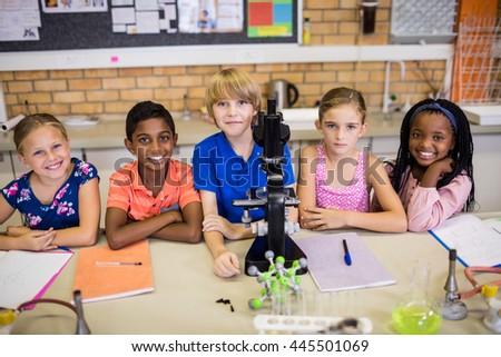 Children posing with microscope at school - stock photo