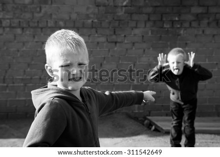 children quarrel and teasing between two boys (brothers, friends) outdoor near red brick wall - stock photo