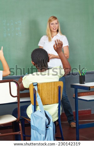 Children raising hands in elementary school math class - stock photo