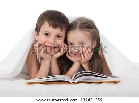 children read a book in bed under the blanket