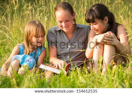 Children reading book on the park together - stock photo