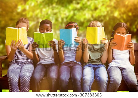 Children reading books at park against trees and meadow in the park - stock photo