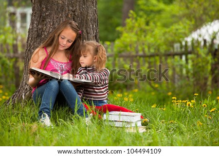 Children reading the book in summer park - stock photo