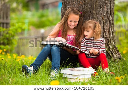 Children reading the book in summer park. - stock photo