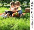 Children reading the book on picnic in summer park - stock photo