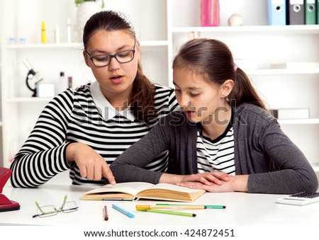 Children reading the book. Two girls, two sisters together - stock photo