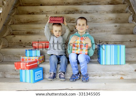 children receive gifts. two happy brother sitting on the stairs with a pile of gifts  - stock photo
