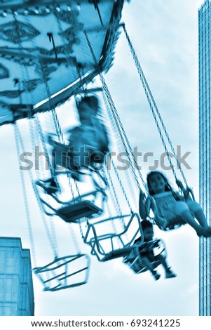 children ride carousel, people in blurred motion, nice mono colored funfair background