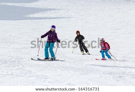 Children ride for adults skier in ski resort - stock photo