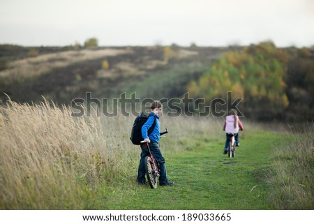 Children riding on bicycles in countryside - stock photo