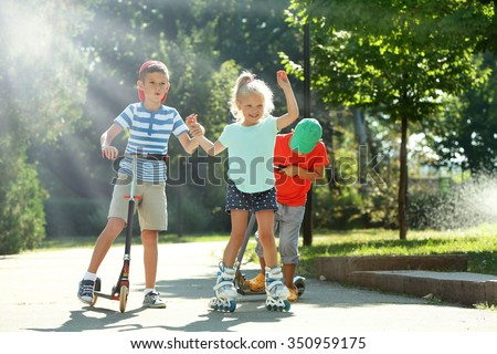 Children riding on scooters and roller skates in park - stock photo