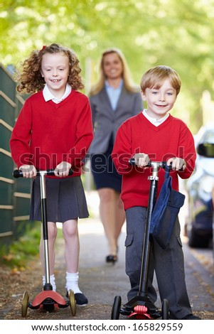 Children Riding Scooters On Their Way To School With Mother - stock photo