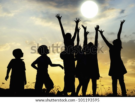 Children rising arms to sun on meadow - stock photo