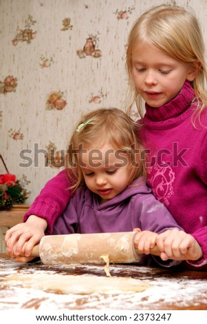 Children rolling out dough for christmas cookies - stock photo