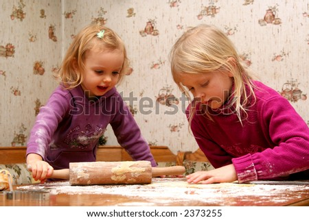 Children rolling out dough for christmas cookies