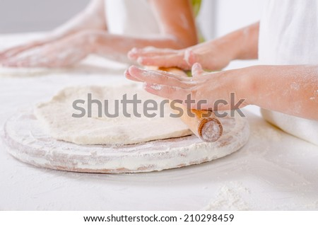Children rolling out dough with a wooden rolling pin to make the base for a homemade pizza - stock photo