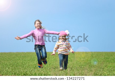 Children run on a green field - stock photo