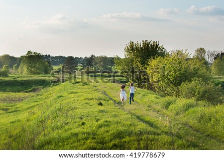 children run on the road, holding hands - stock photo
