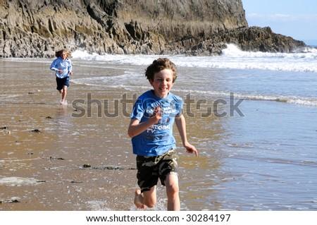 children running along beach - stock photo