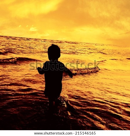 children  running at the beach on the sunset  time - stock photo