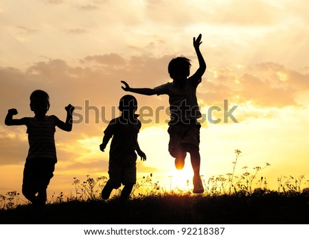 Children running on meadow at sunset - stock photo