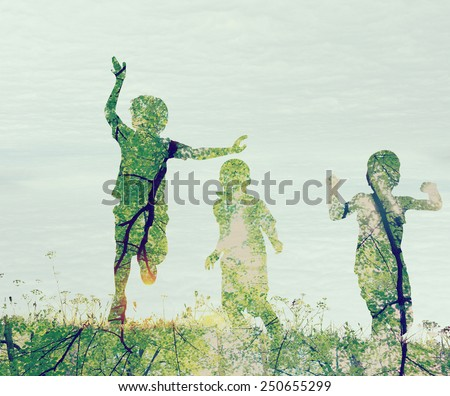 Children running on meadow at sunset double exposure