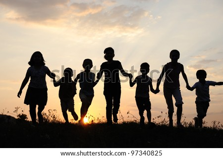Children running on meadow at sunset time