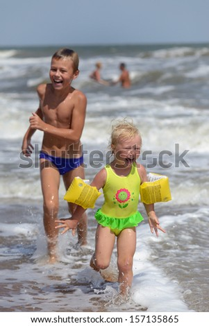 children running on the beach - stock photo