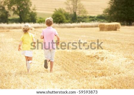 Children Running Through Summer Harvested Field - stock photo