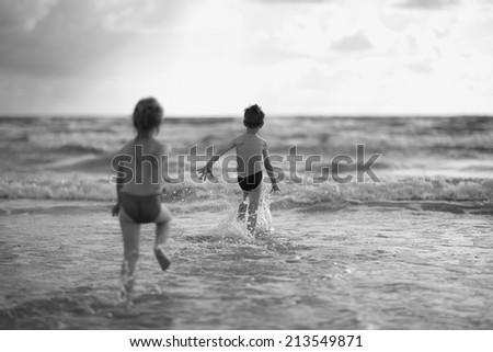 Children running to the sea - stock photo