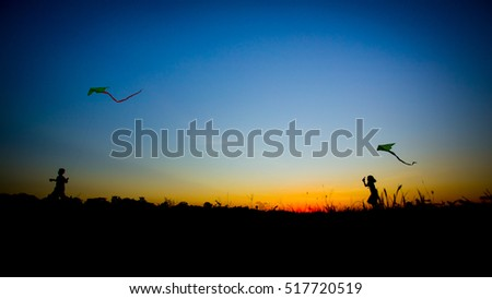 Children running with kite. Silhouette of boy and girl flying a kite in sunset background.