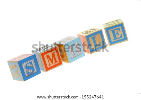 Children's Alphabet Blocks spelling the words smile on white background on Education - stock photo