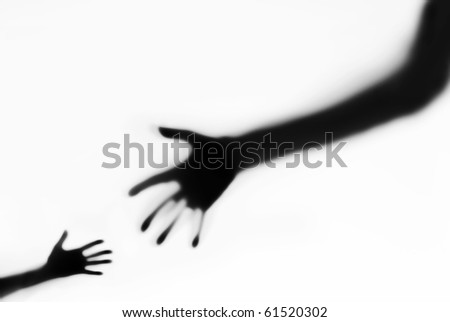 Children's and adult hands stretched to each other through matte glass - stock photo