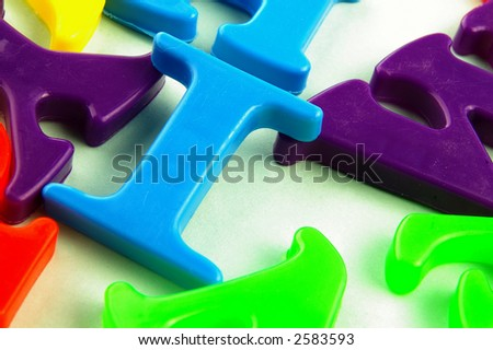 Children's assorted colorful plastic letters closeup, on textured surface