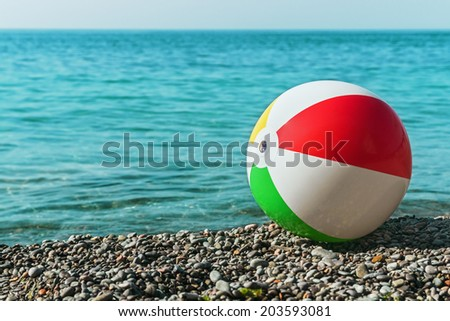 children's ball on the beach against the sea. Focus on the valve to inflate the ball - stock photo