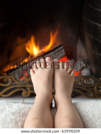 Children's bare feet are heated in the fire in the fireplace with a brass openwork lattice - stock photo