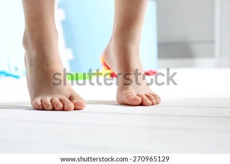 Children's bare feet. Child's bare feet on the wooden floor   - stock photo