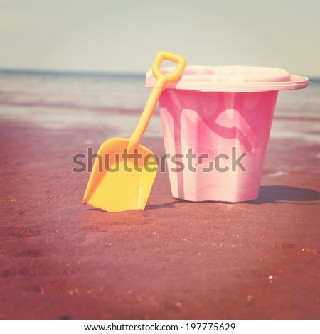 Children's beach toys - bucket and shovel on sand on a sunny day  - stock photo