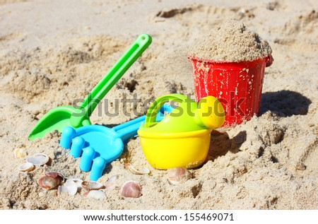 Children's beach toys - bucket, spade and shovel on sand on a sunny day  - stock photo